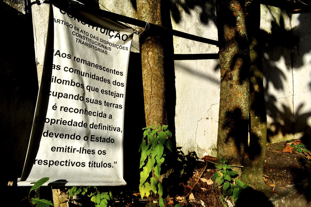 A sign in front of driveway to quilombo Sacopã in Rio de Janeiro announces that the property is a quilombo. In English, it re