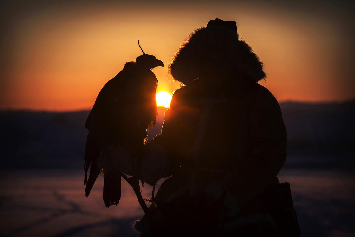 Chinese Kazakh eagle hunter Bolat Beysenbay sits atop his horse as he holds his eagle before a local competition in the mount