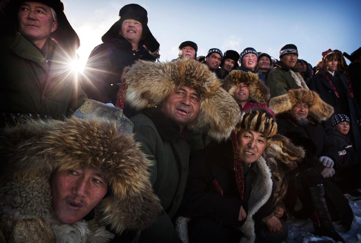 Spectators watch a Chinese Kazakh eagle hunter release his bird during a local competition in the mountains of Qinghe County,