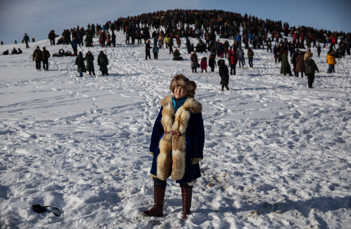 A Chinese Kazakh boy watches during a local eagle hunting competition in the mountains of Qinghe County, China on Jan. 31, 20