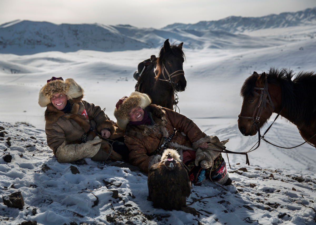 Chinese Kazakh eagle hunters laugh together as they rest during a local competition in the mountains of Qinghe County, China,