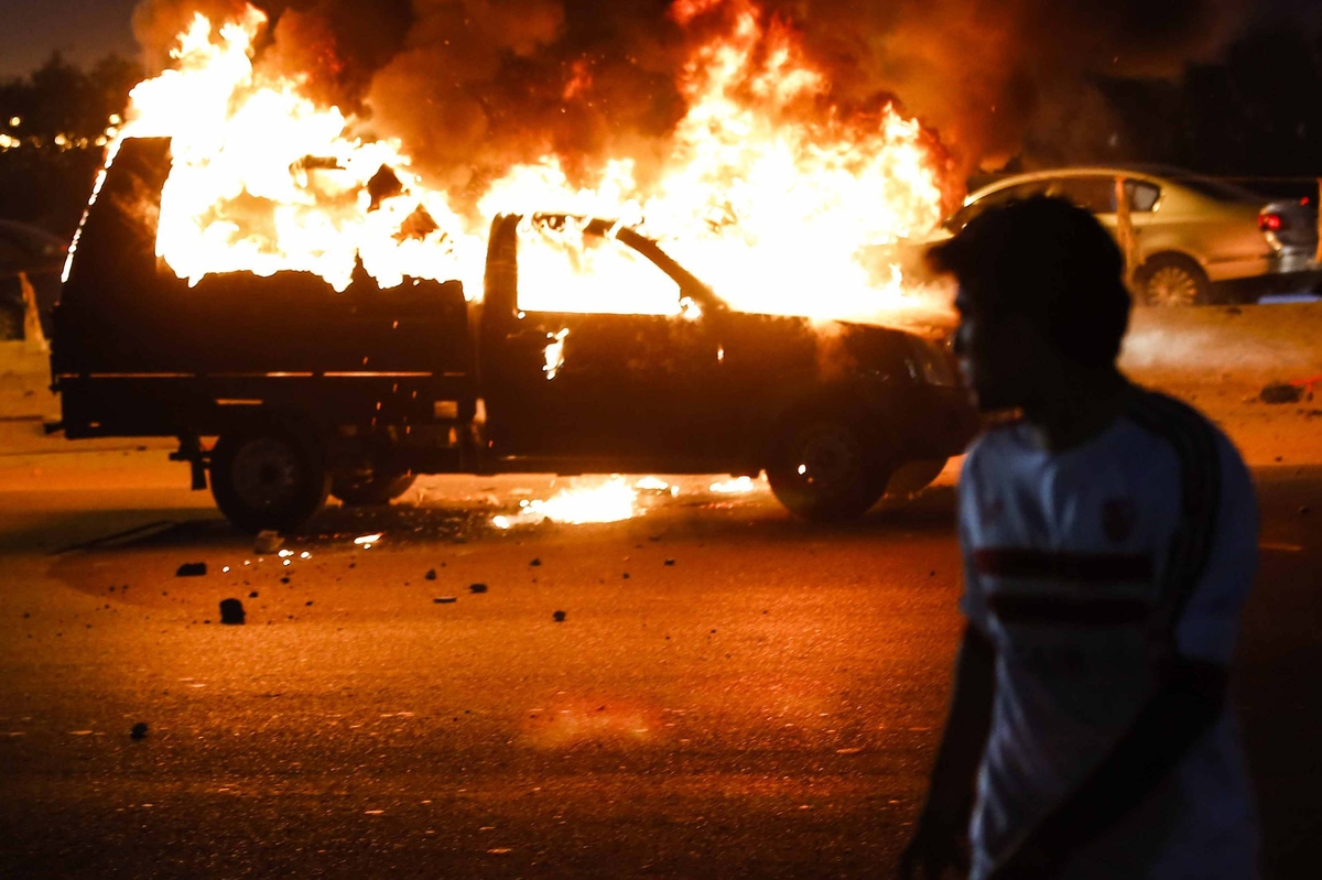 CAIRO, EGYPT - FEBRUARY 08:  A man walks past a burning vehicle during the clashes between soccer fans and policemen outside