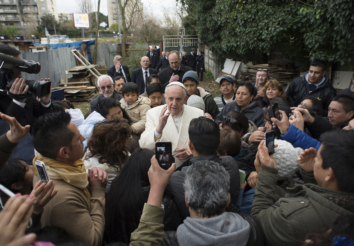 Pope Francis is welcomed by residents of a refugee camp in Ponte Mammolo, in the outskirts of Rome, as he made an unscheduled