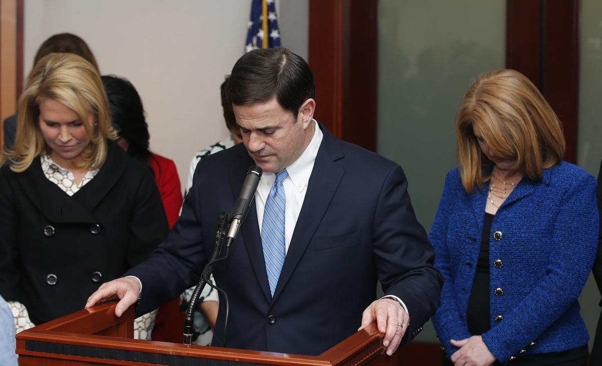 El gobernandor de Arizona Doug Ducey, al centro, junto a su esposa Angela Ducey, a la izquierda, y la congresista republicana