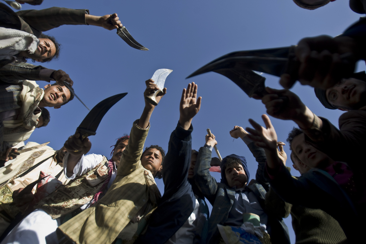 Supporters of Houthi Shiites wave traditional daggers and dance as they celebrate the fourth anniversary of the uprising in S
