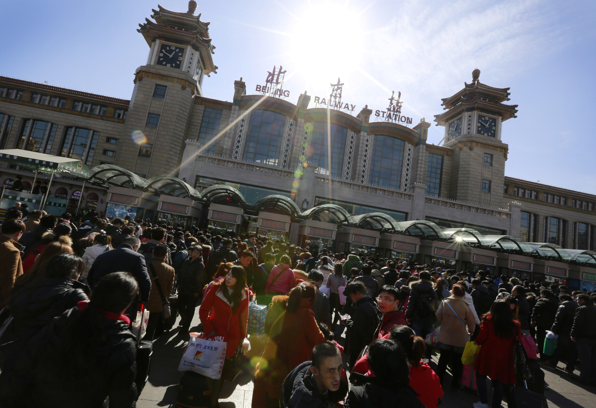 Chinese travelers queue up at the main entrance of the Beijing railway station to catch their trains in Beijing, China Tuesda