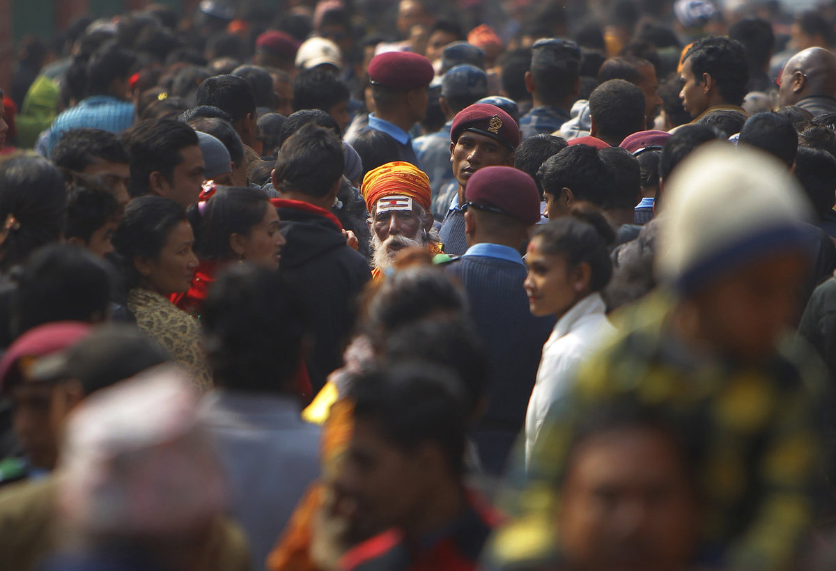A Hindu holy man walks amid a sea of devotees at the Pashupatinath temple during Shivratri festival in Kathmandu, Nepal, Tues