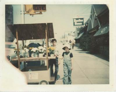 """<em>""""Here I am as a kid selling flowers from a cart in Brooklyn. My brother (standing in the back) was totally not into it. T"""