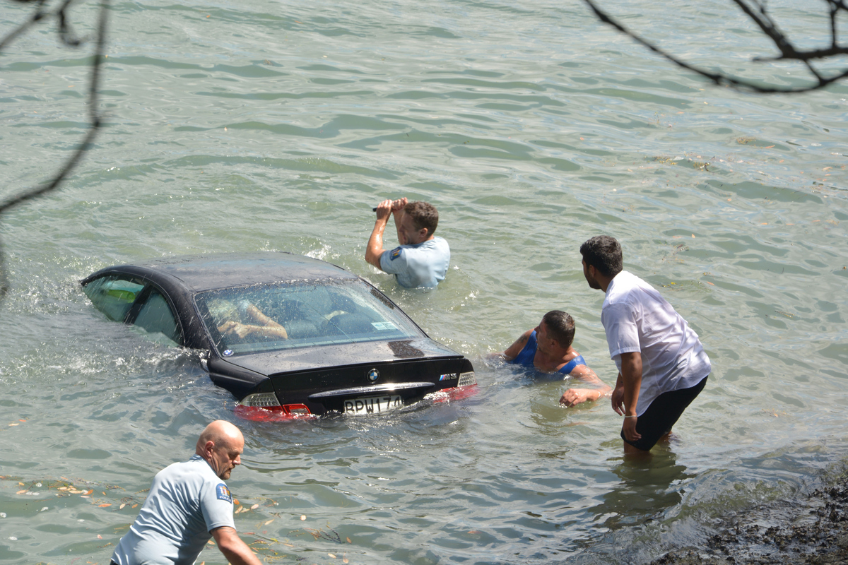 Rescuers plunge into the water to save a woman, whose car went into the water at Northcote Point on February 17, 2015 in Auck