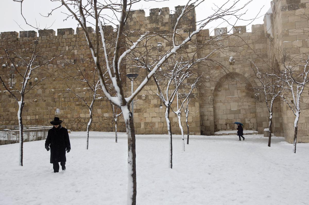 An ultra-Orthodox Jewish man walks in the snow near the Jaffa gate in Jerusalem's Old City, Friday, Feb. 20, 2015. (AP Photo/