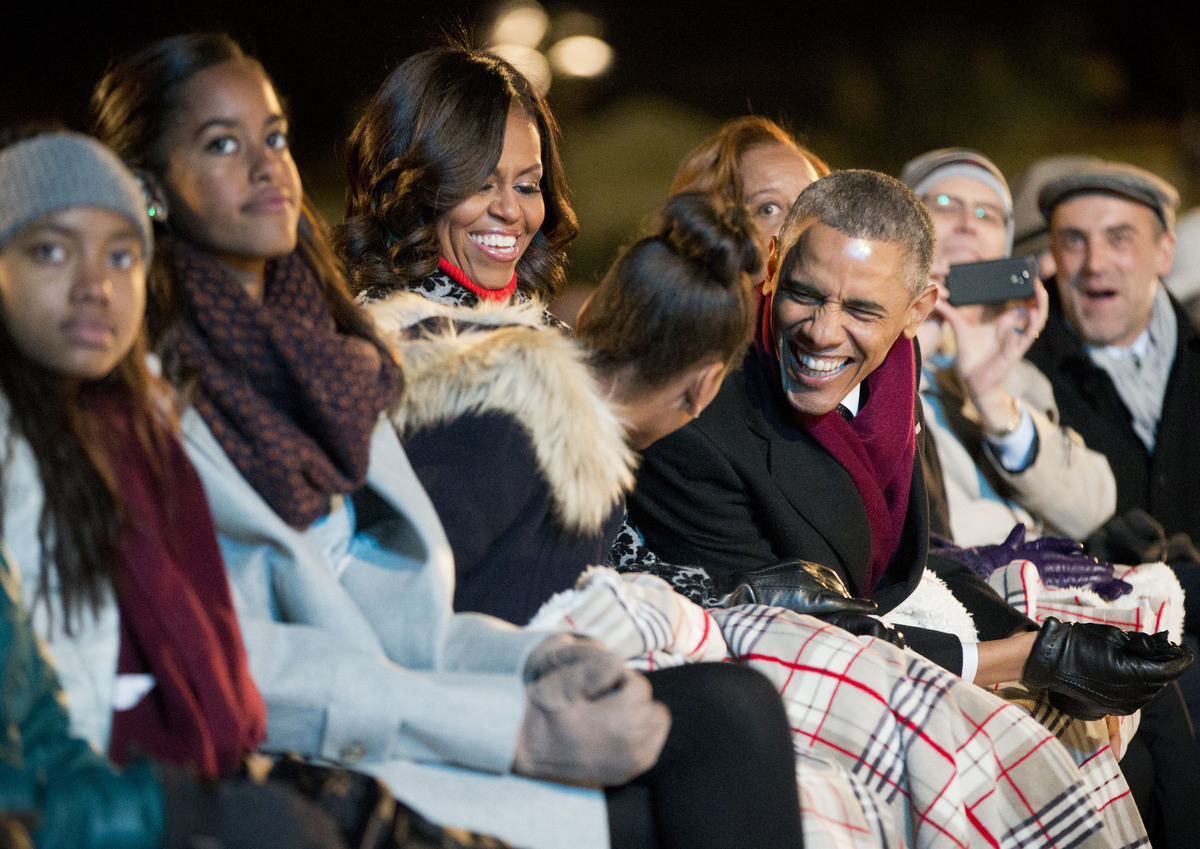 President Barack Obama leans over to talk with his daughter Sasha as they sit with first lady Michelle Obama and Malia and wa