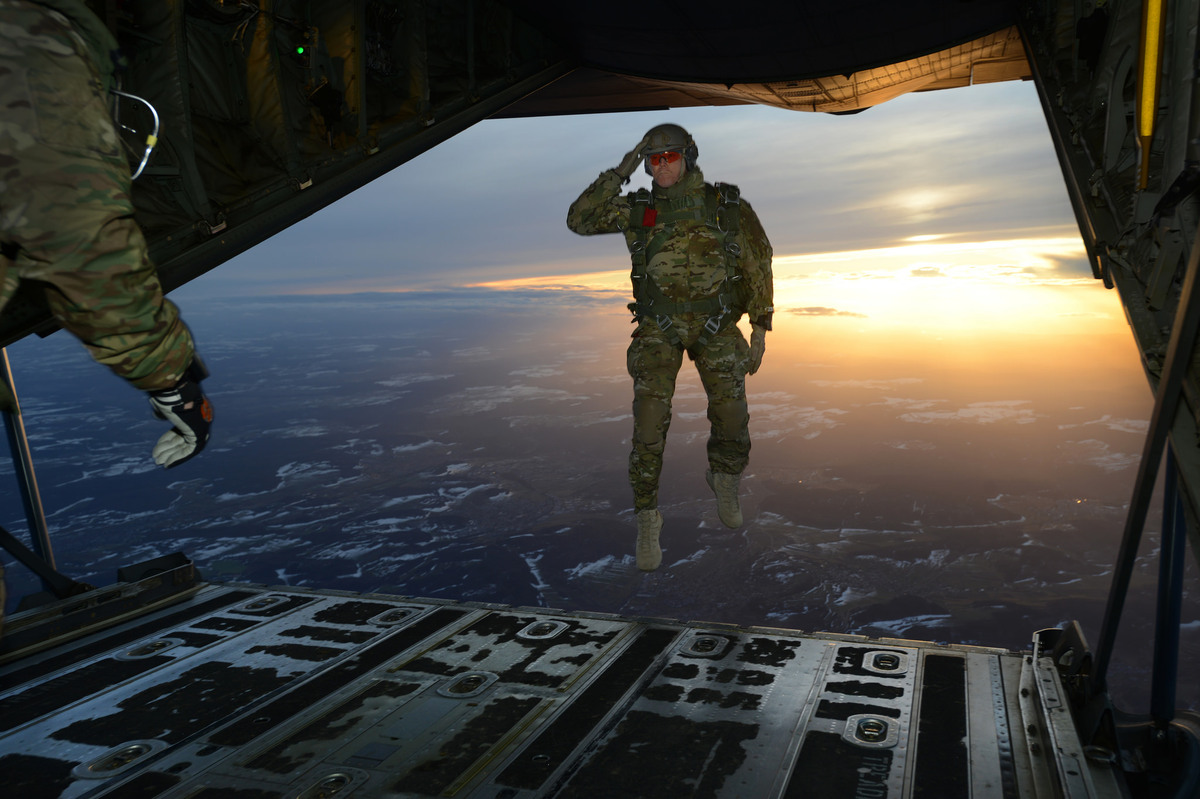 A U.S. Soldier assigned to 1st Battalion, 10th Special Forces Group (Airborne) salutes his fellow Soldiers while jumping out