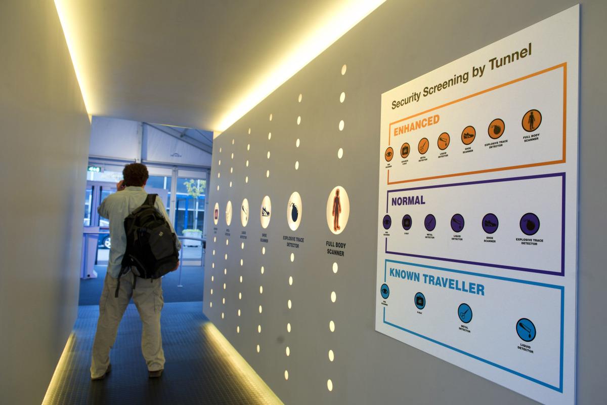A person walks through a model of a scanning corridor at the International Air Transport Association Aviation Security (IATA