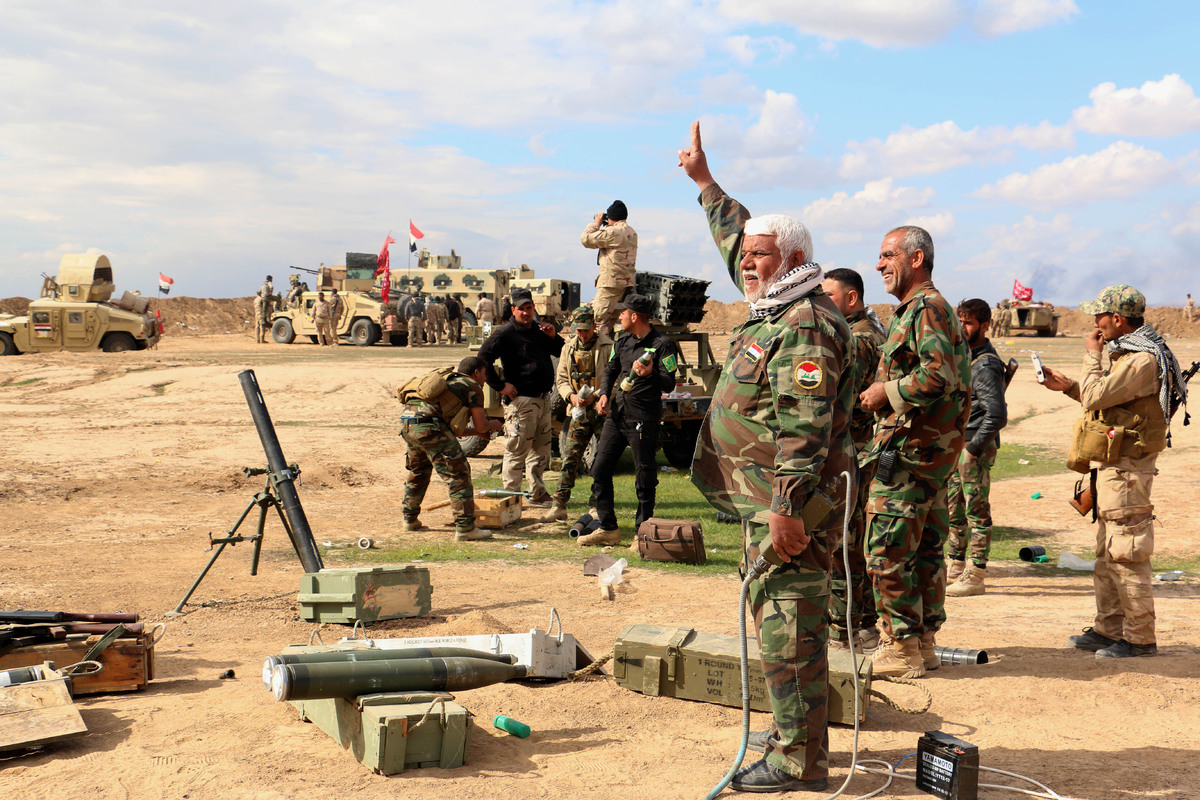 In this Wednesday, March 4, 2015 photo, Iraqi army soldiers and volunteers prepare to launch mortar shells and rockets agains