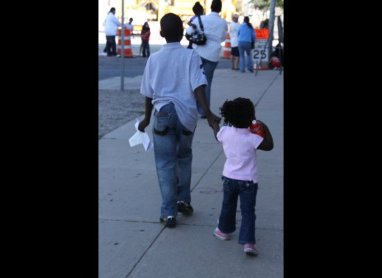 An 11-year-old keeps a close grip on his younger sister as they follow their mom to the back of the line for the Healthy Kids