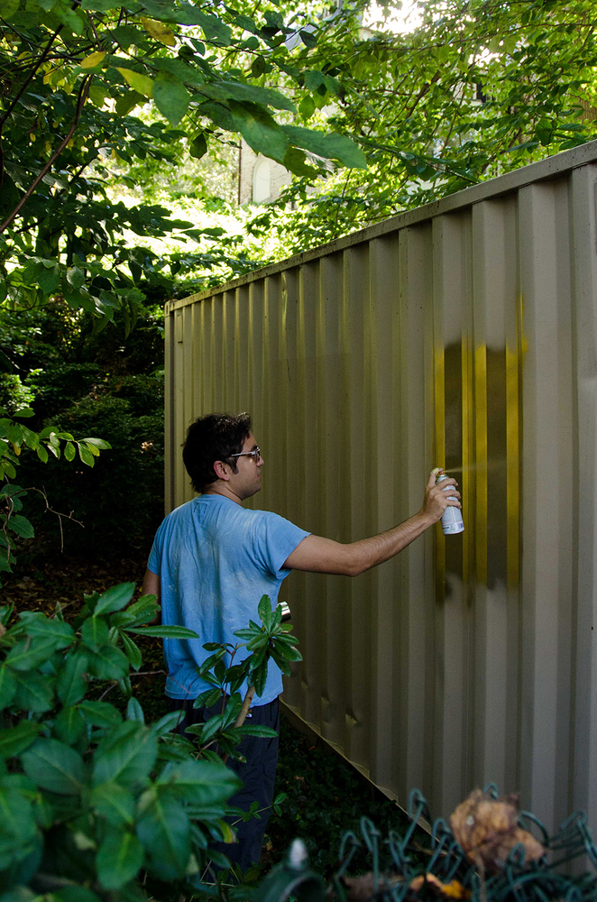 Amar spraypainting the container gold -- making the mundane sacred