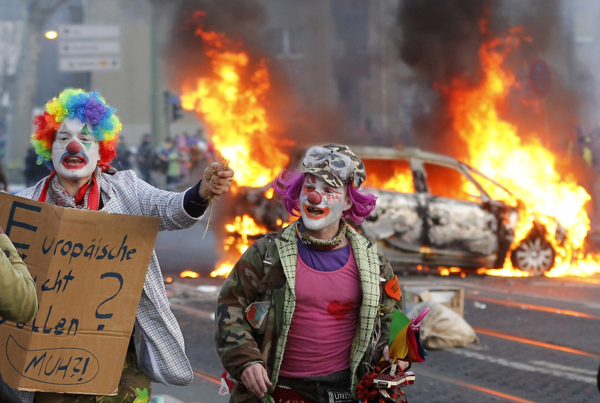 Demonstrators dressed as clowns pass by a burning police car Wednesday, March 18, 2015 in Frankfurt, Germany.   (AP Photo/Mic