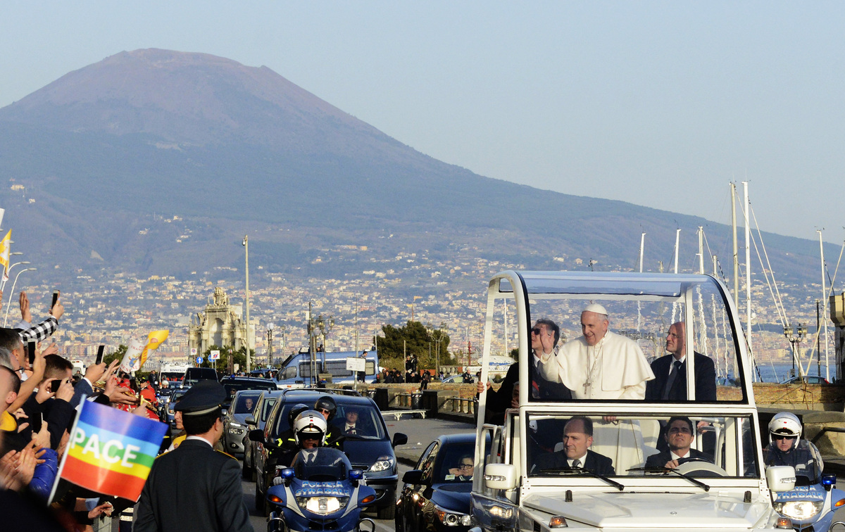 Pope Francis waves to faithful as he arrives for a meeting with young people in Naples, Italy, Saturday, March 21, 2015. Fran
