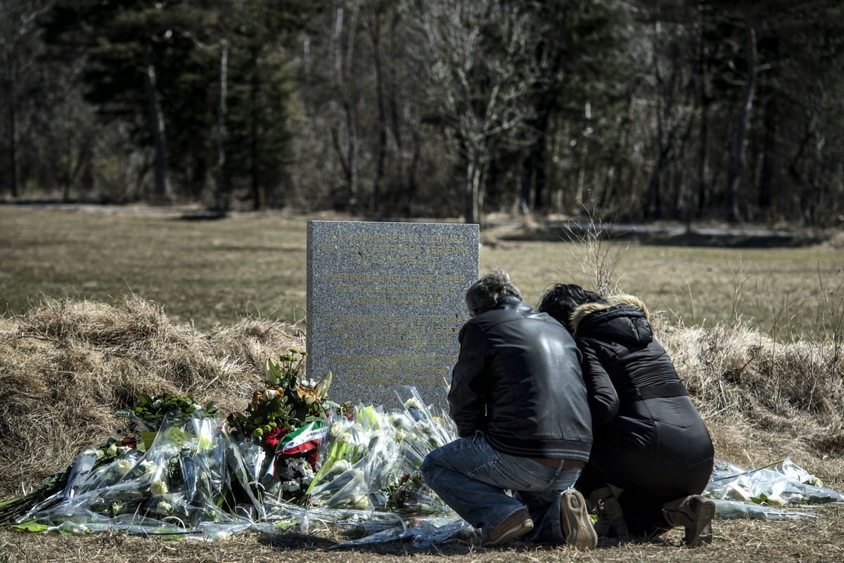 People pay tribute in front of a stele, carved in French, German, Spanish and English, in memory of the victims of the German