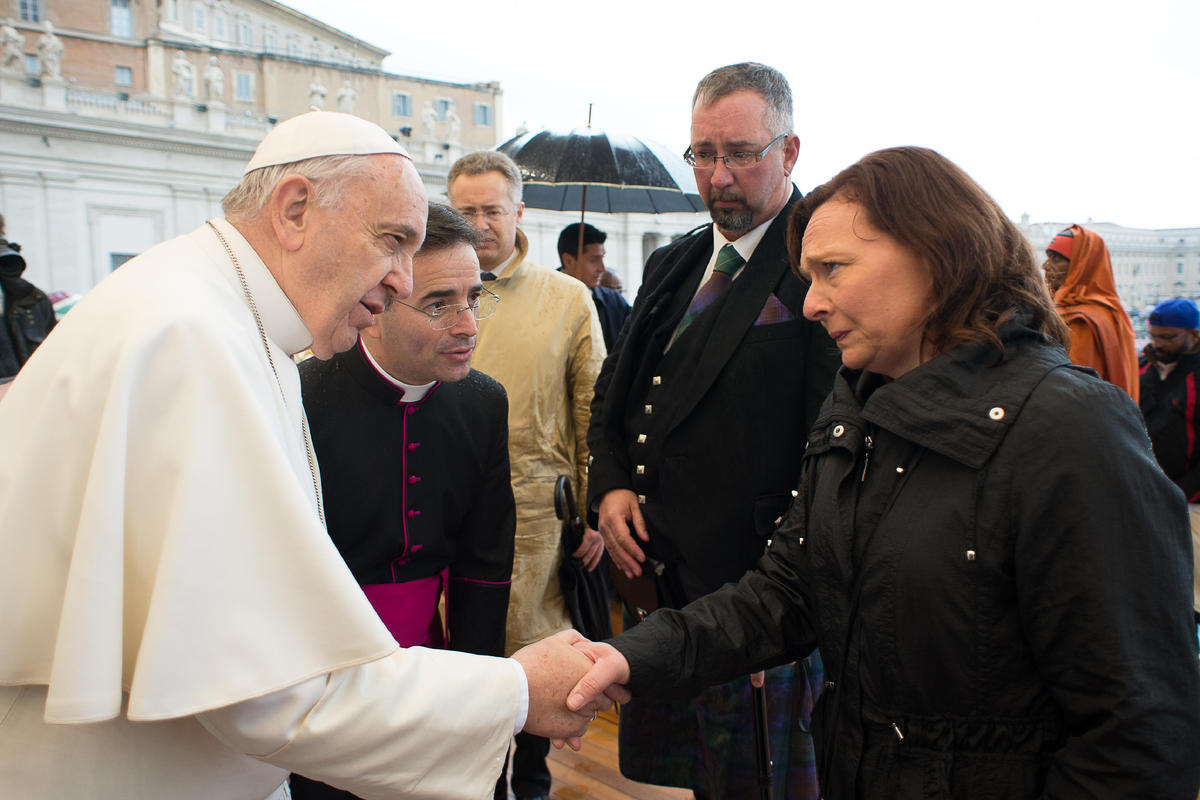 Pope Francis greets Barbara Henning, right, as Michael Haines, second from right, looks at them, during the pontiff's weekly