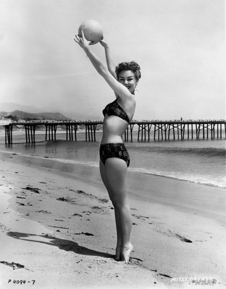 1955:  American actor Mitzi Gaynor, wearing a bikini, holds a volleyball over her head on a beach in a full-length promotiona