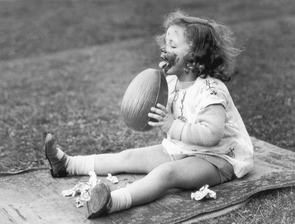 Girl enjoys a huge chocolate Easter egg in 1930.