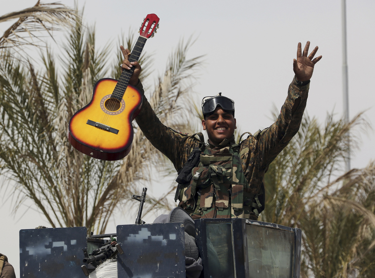 An Iraqi soldier celebrates with his guitar atop his armored vehicle on the main road between Baghdad and Tikrit, April 3, 20