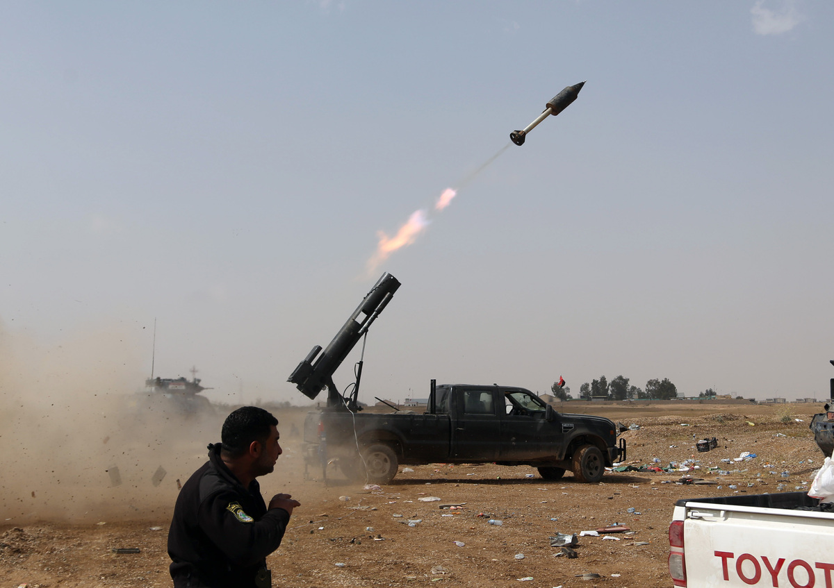 In this Monday, March 30, 2015 file photo Iraqi security forces launch a rocket against Islamic State extremist positions dur