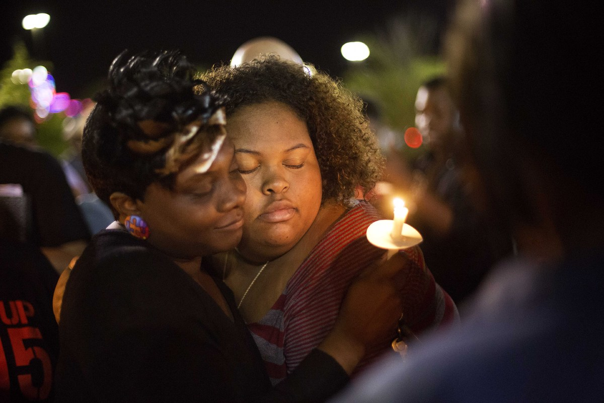 Chasyn Carter, right, of North Charleston, S.C., embraces Candice Ancrum, of Summerville, S.C., during a candlelight vigil ou