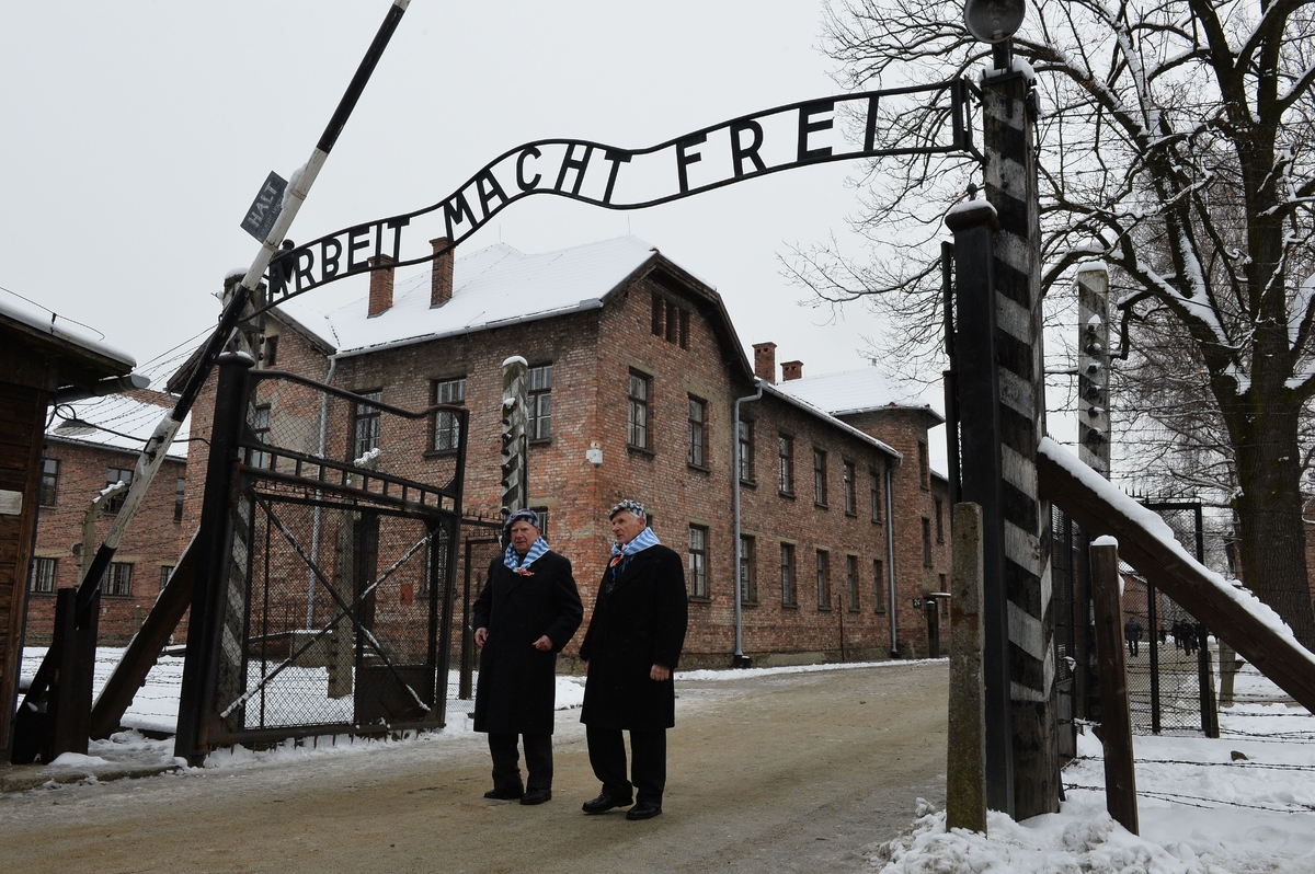 Auschwitz survivors walk through the gate of the former Auschwitz concentration camp as they arrive to attend fesitivities to