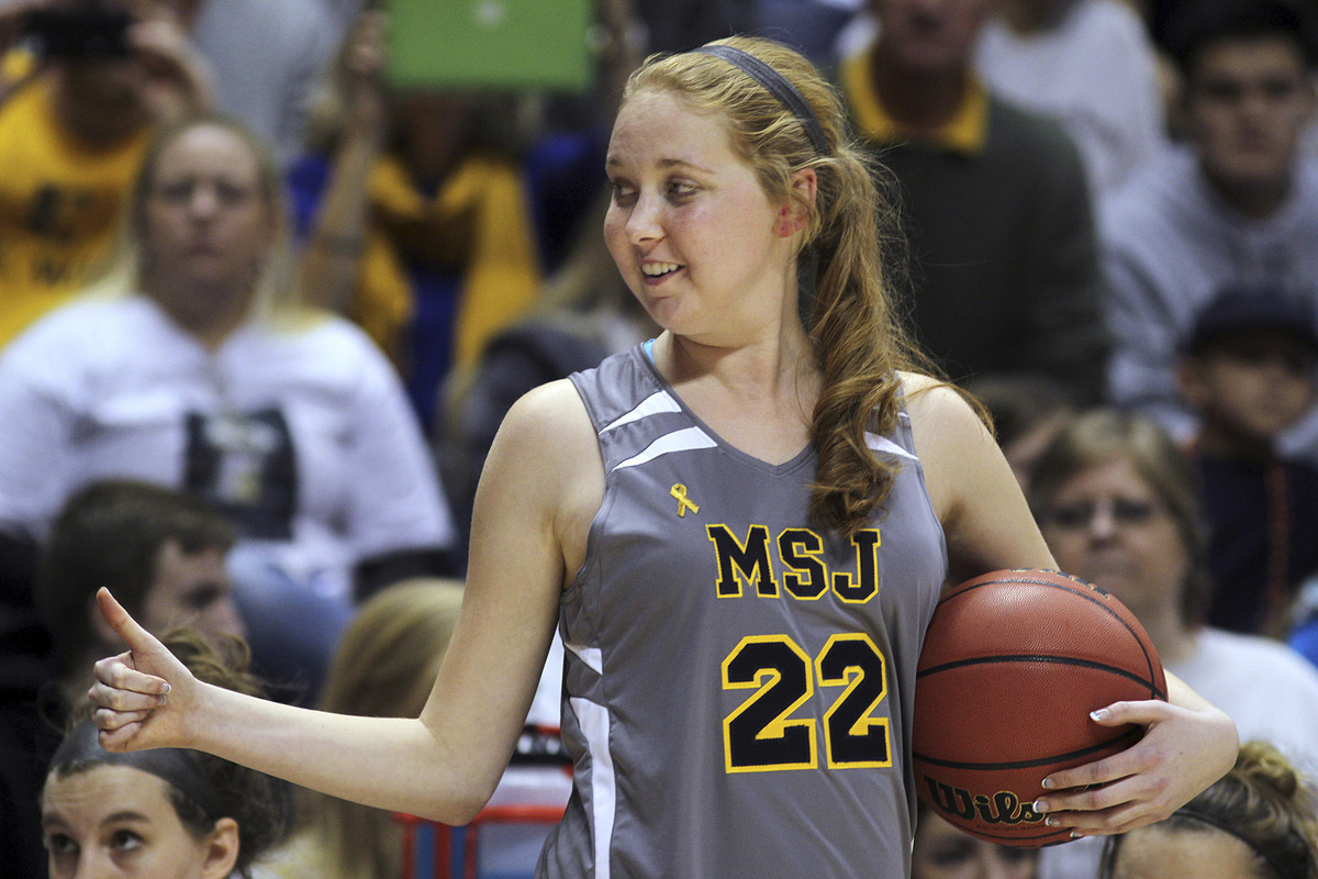In this Nov. 2, 2014, file photo, Mount St. Joseph's Lauren Hill gives a thumbs-up as she holds the game ball during her firs