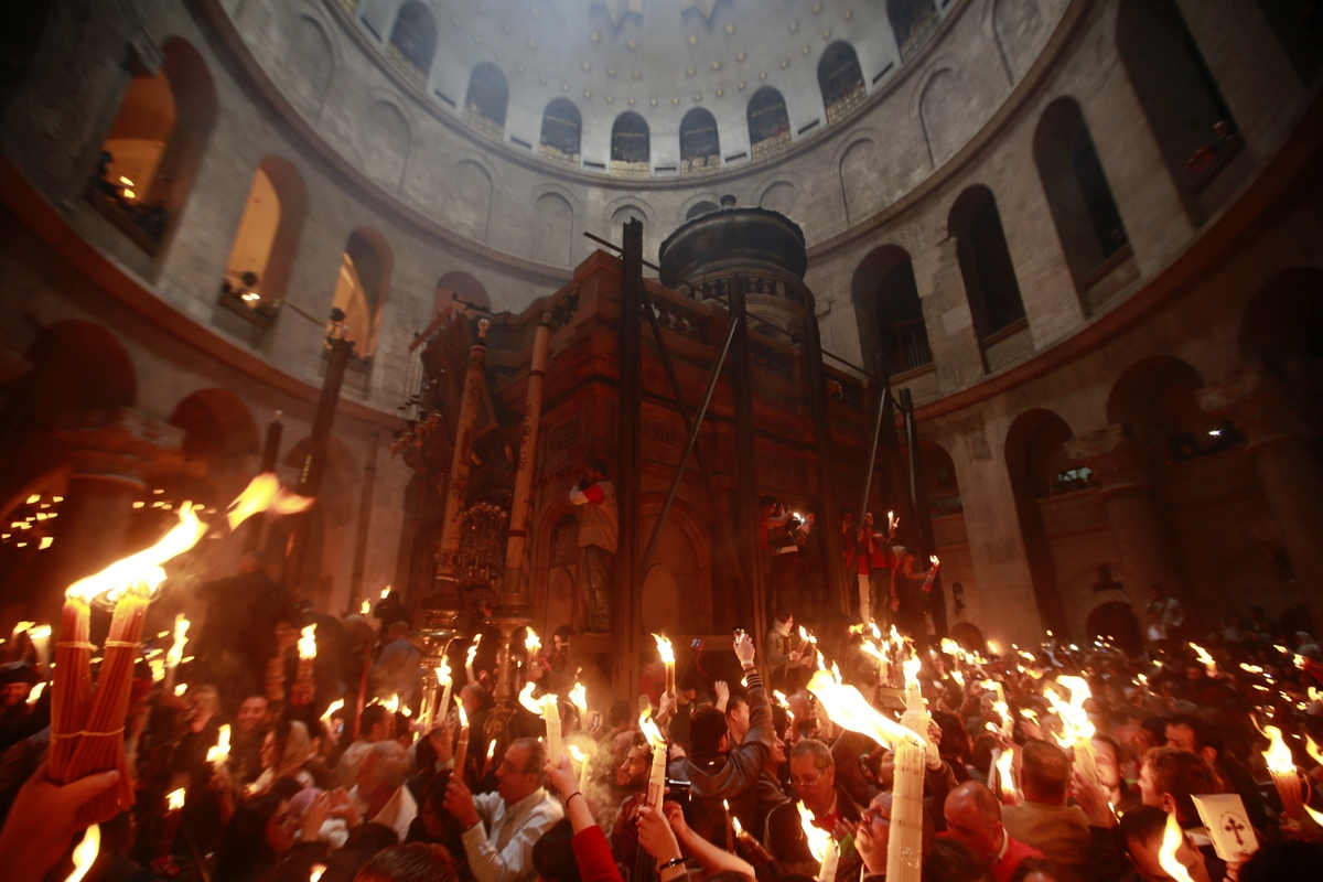 Christian Orthodox worshipers hold up candles lit from the 'Holy Fire' as thousands gather in the Church of the Holy Sepulchr
