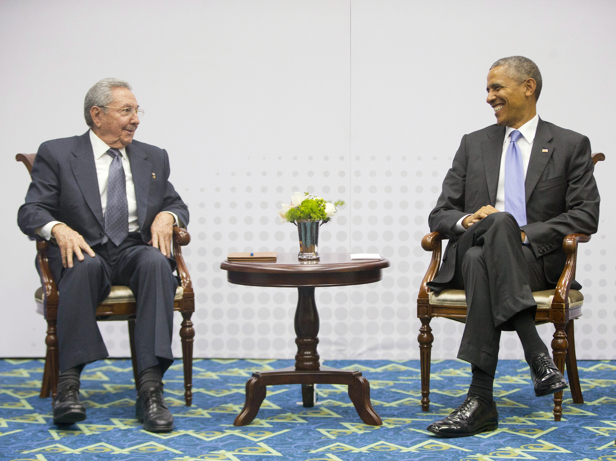 US President Barack Obama, right, smiles as he looks over towards Cuban President Raul Castro, left, during their meeting at