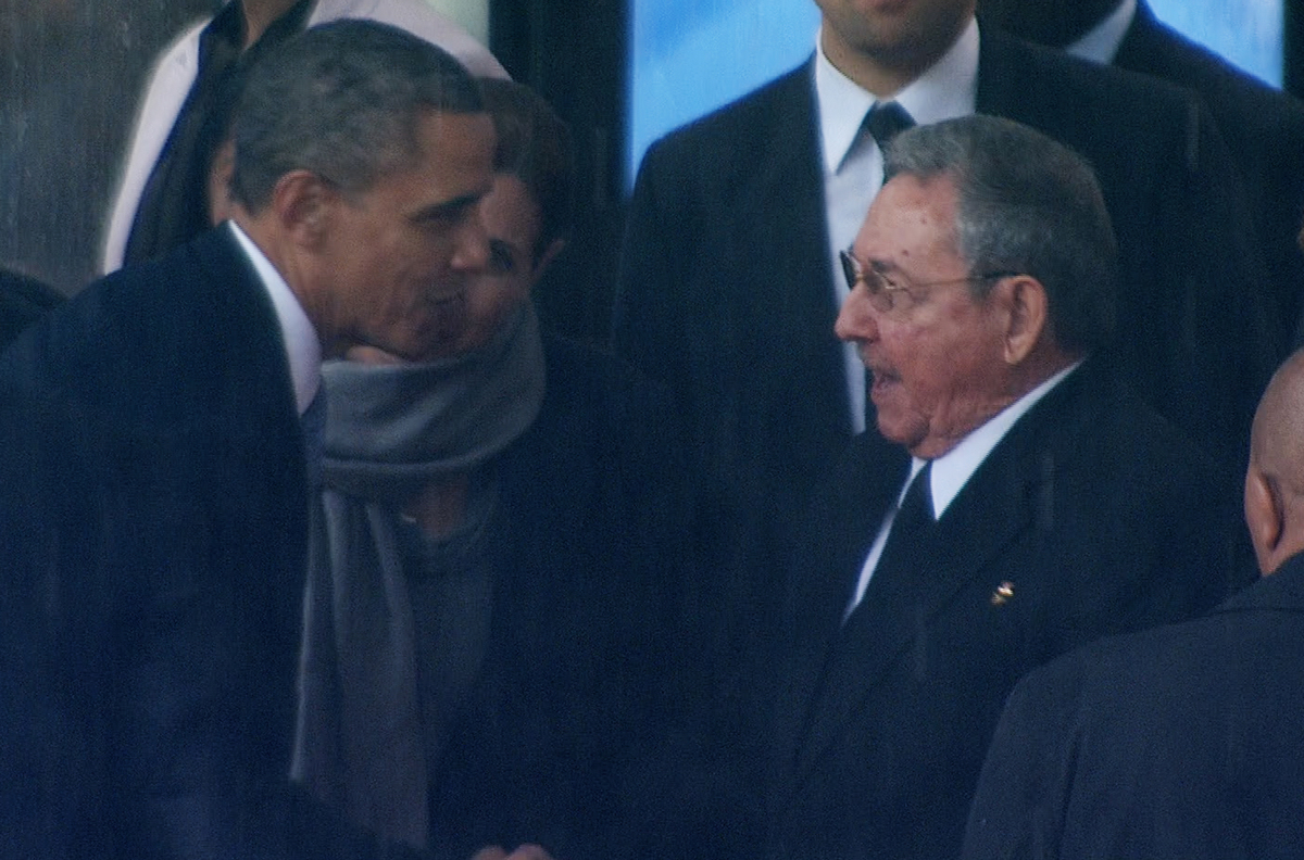In this image from TV, US President Barack Obama shakes hands with Cuban President Raul Castro at the FNB Stadium in Soweto,