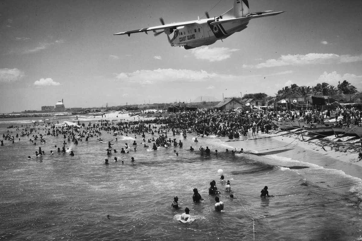 An Indian Coast Guard plane flies too low over the protesting villagers, who have ventured into the sea as a part of their Ja