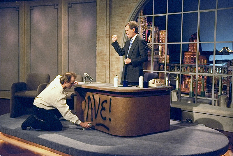 """Bill Murray spray paints Dave's desk on the first taping of """"The Late Show with David Letterman"""" August 30, 1993 on the CBS T"""