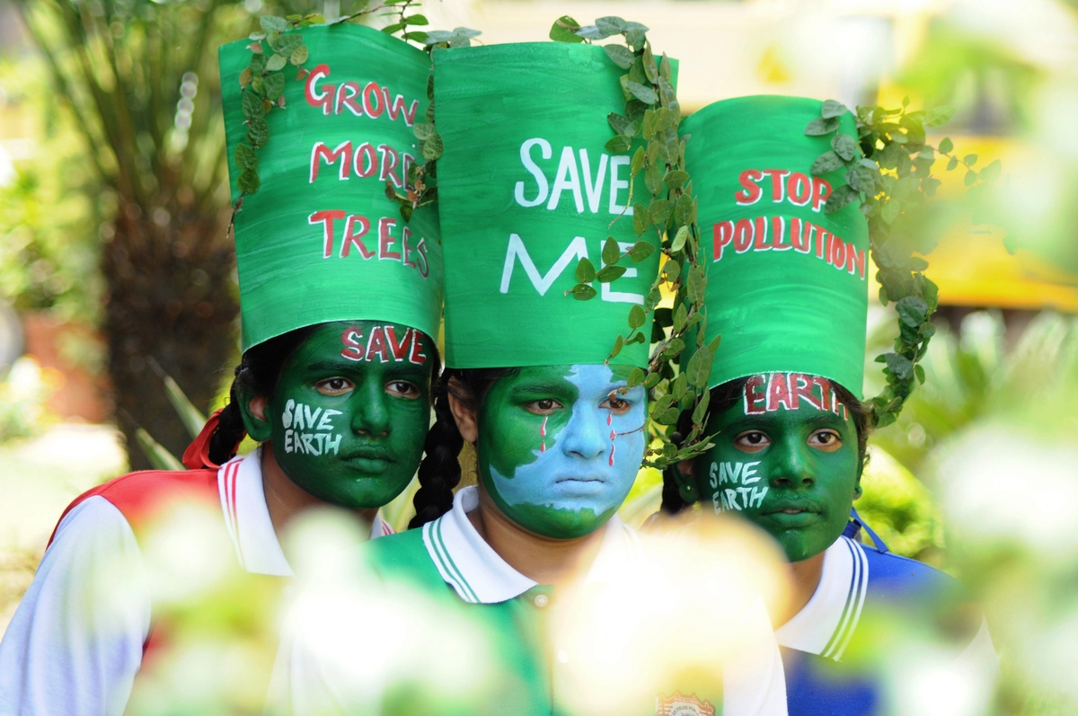 Young Indian girls pose with their painted faces during a 'Save Earth' awareness programme on the eve of World Earth Day at a