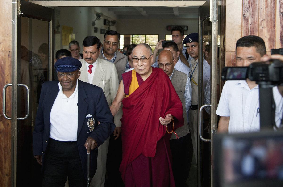 Archbishop Desmond Tutu, left, is received by Tibetan spiritual leader the Dalai Lama at the Kangra airport in Dharmsala, Ind