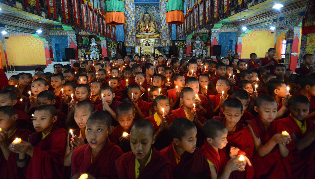 Novice Buddhist monks light candles and offer prayers for victims of Nepal's earthquake, in Bodhgaya, India, Sunday, April 26
