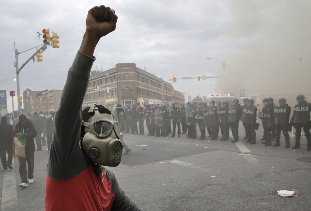A demonstrator raises his fist as police stand in formation as a store burns, Monday, April 27, 2015, during unrest following