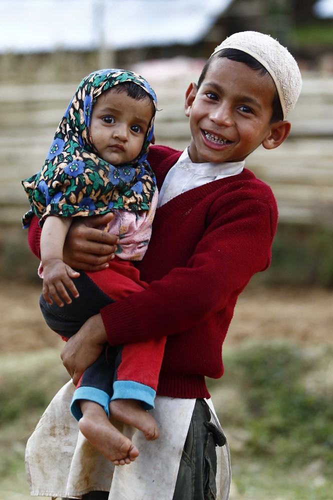 GORKHA, NEPAL - APRIL 29: A Nepalese child carries a baby in Deragaun village of Nepal's Gorkha district on April 29, 2015 af