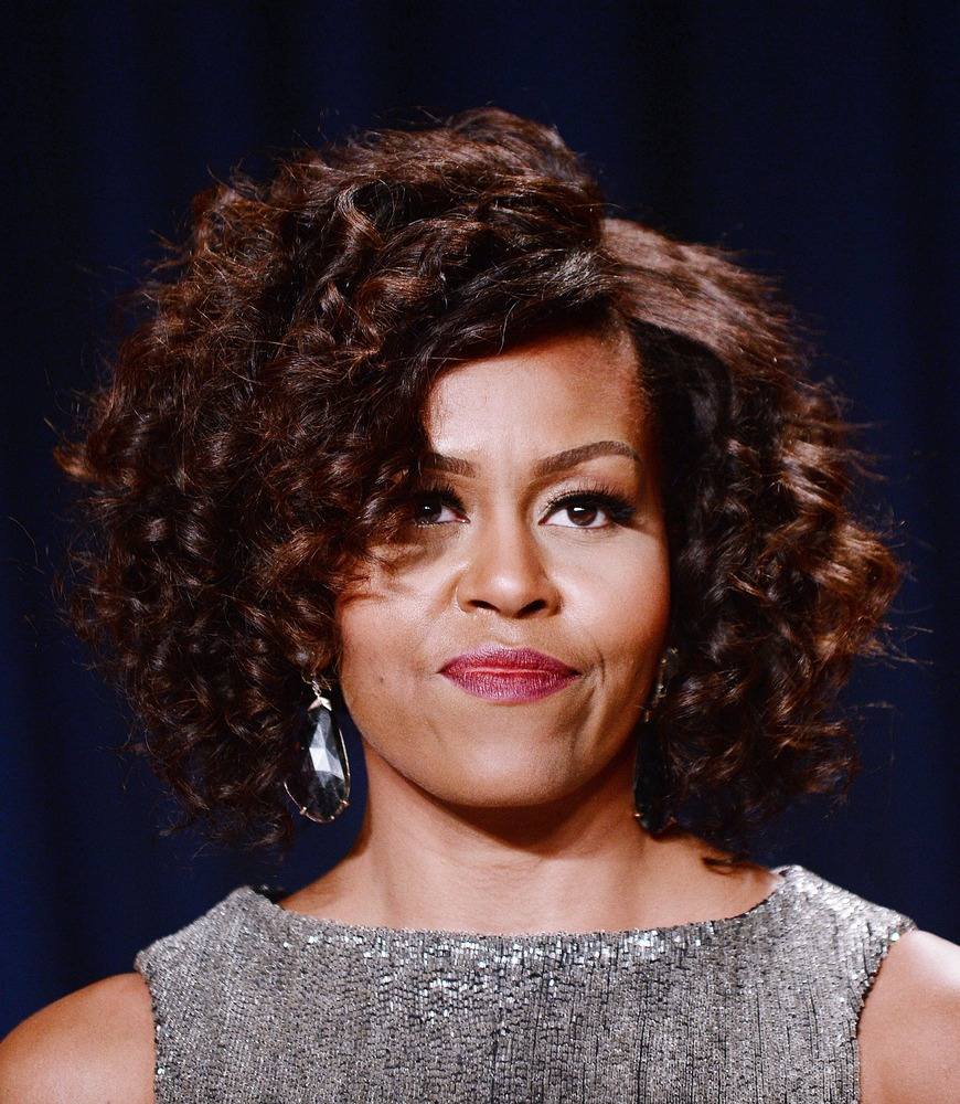 The first lady's voluminous curls frame her face perfectly and draw our attention to her groomed brows and burgundy pout. <em