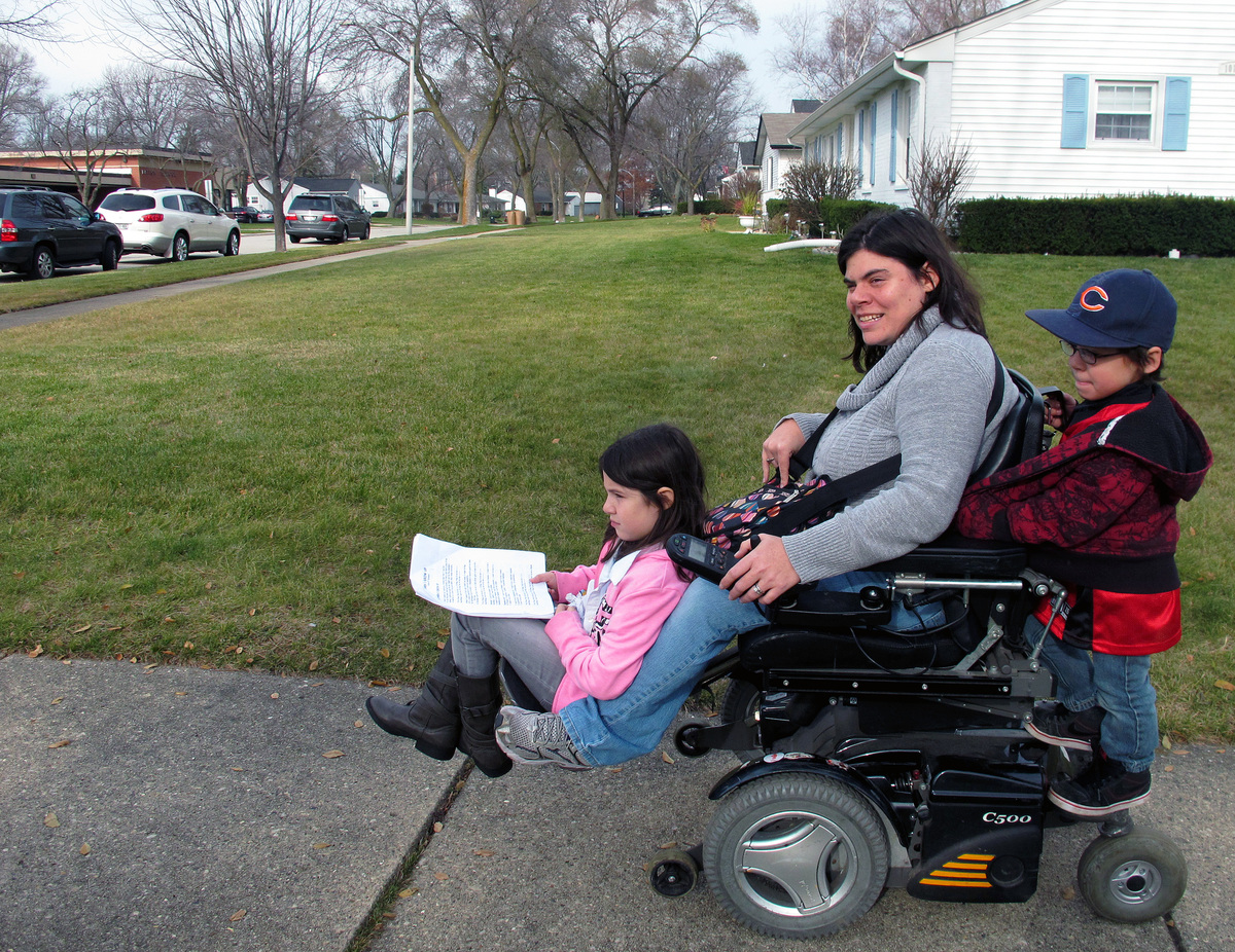 Twins Abigail and Noah Thomas, 8, ride on the motorized wheelchair of their mother, Jenn Thomas, on their way to a school boo
