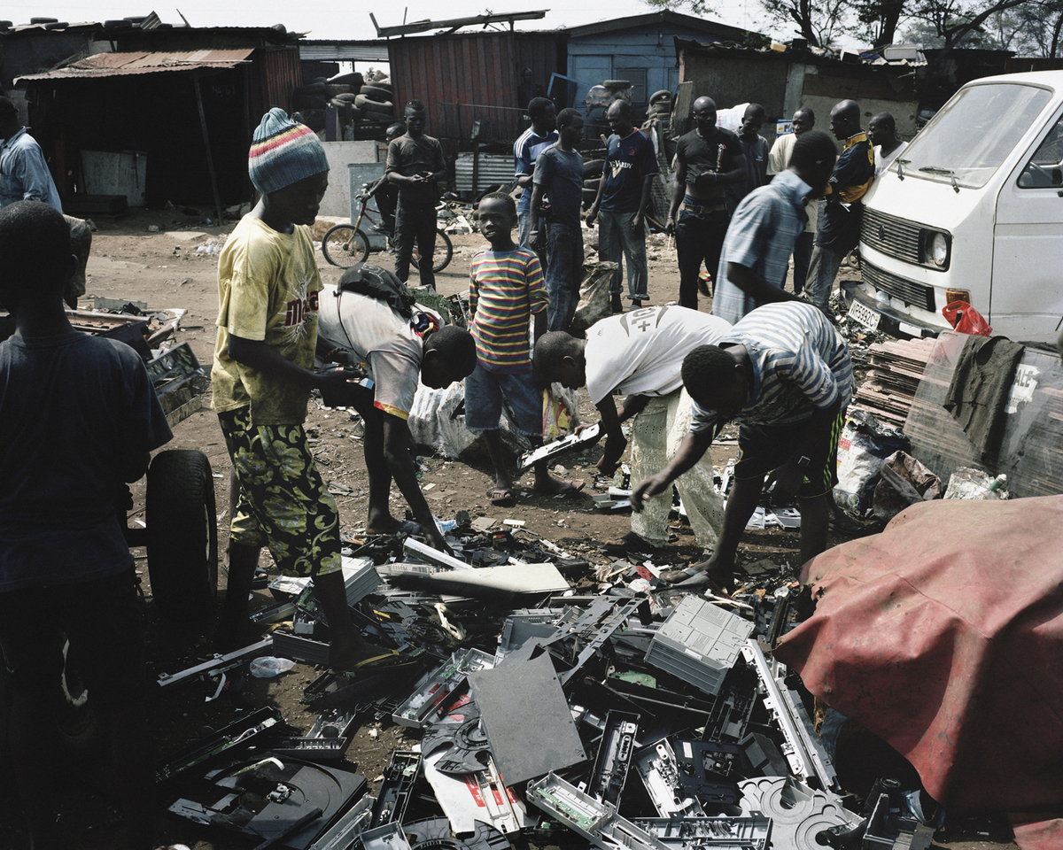 Agbobloshie, Accra, Ghana. Young boys selecting electronic waste in front of the Agbobloshie landfill. The flow of trucks unl