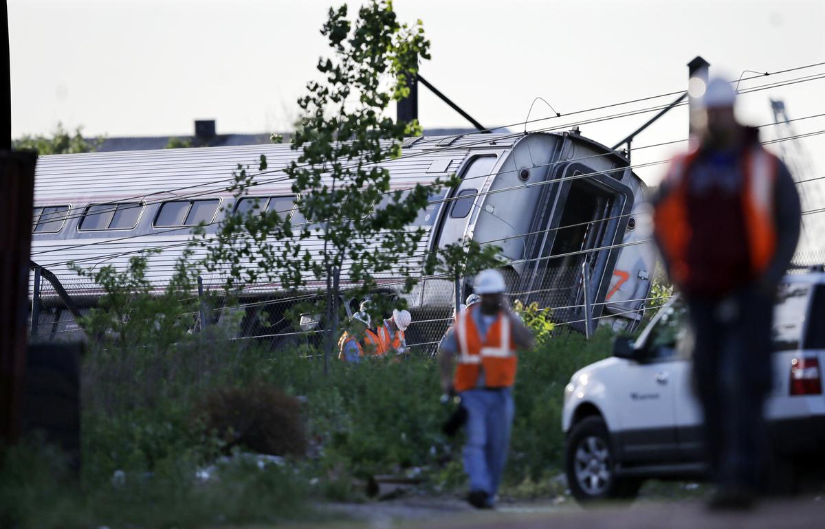 Emergency personnel walk near the scene of a deadly train wreck, Wednesday, May 13, 2015, in Philadelphia. An Amtrak train he