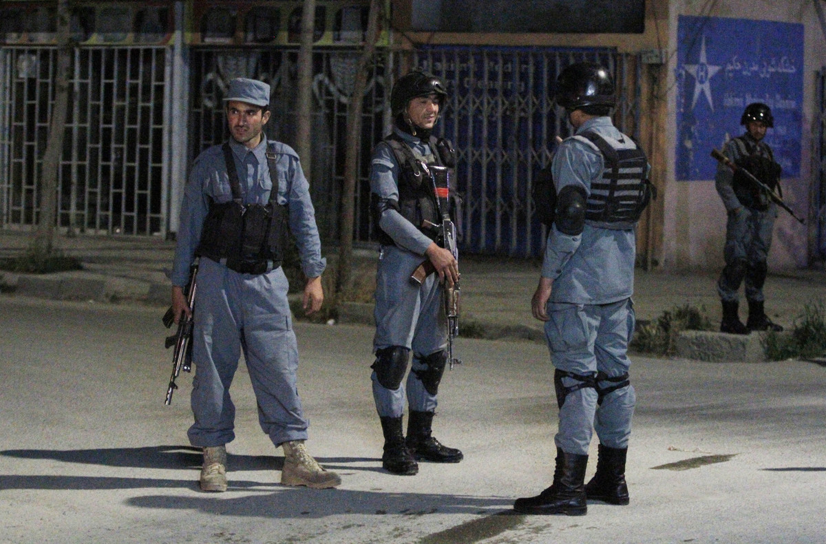 Afghan policemen stand guard near the Park Palace Hotel after an attack by Taliban militants, in Kabul, Afghanistan, Wednesda