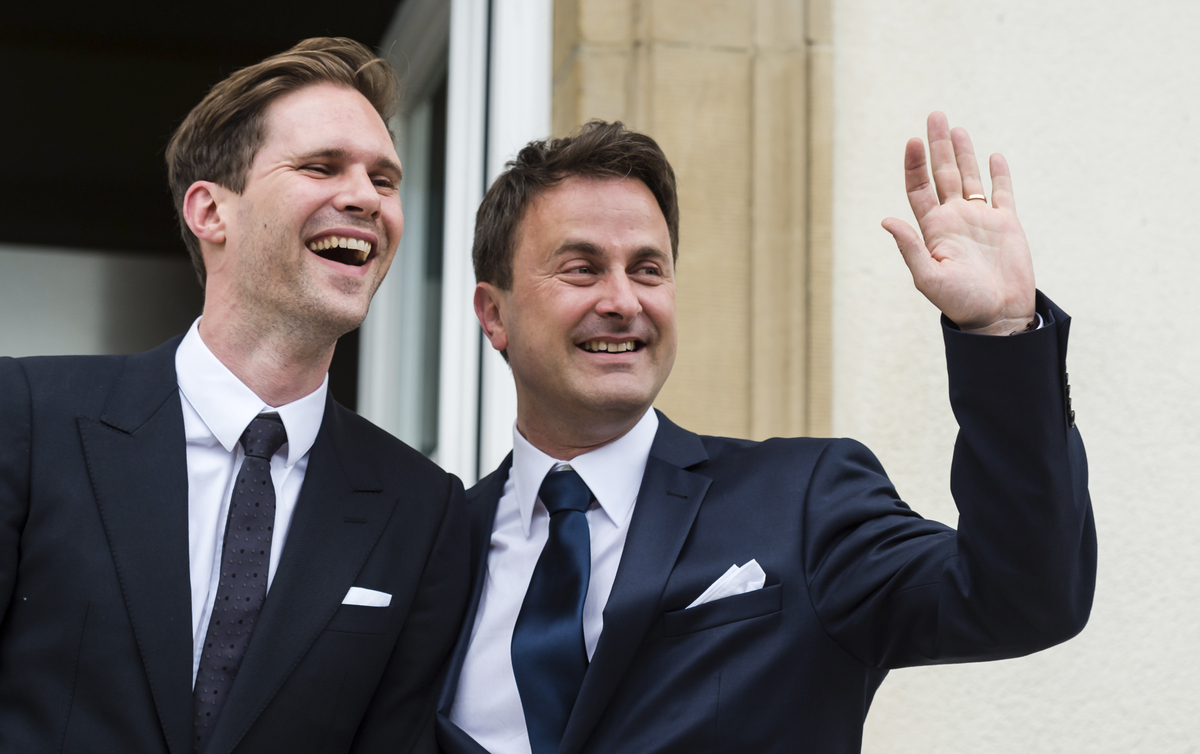 Luxembourg's Prime Minister Xavier Bettel, right, waves as he stands next to his partner Gauthier Destenay after their marria