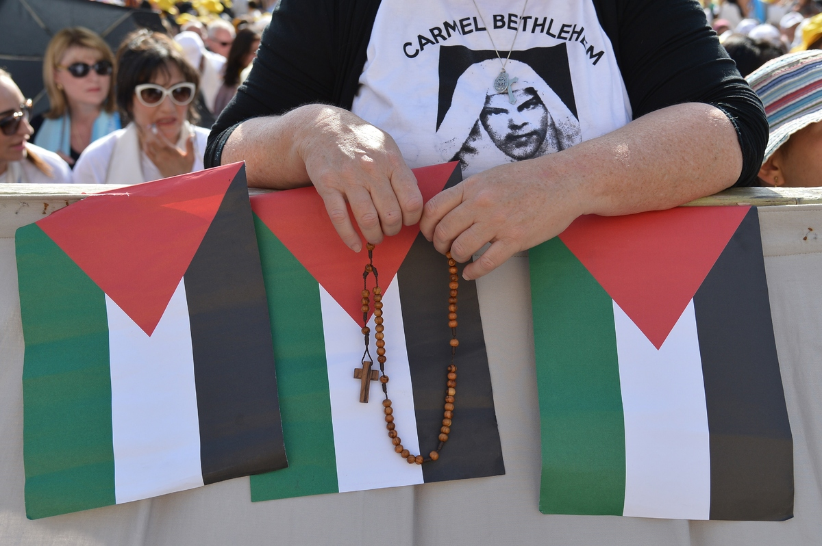 A pilgrim stands behind Palestinian flags before a holy mass in St Peter's square for the canonization of four blessed nuns,