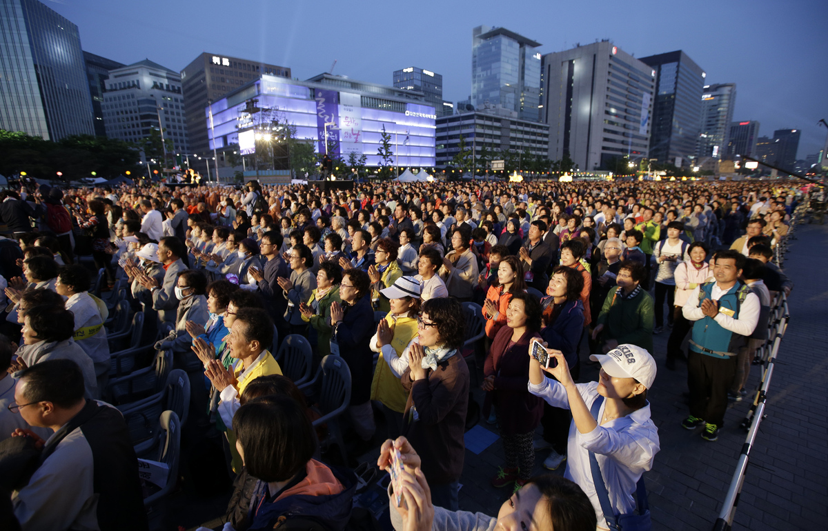 Buddhists pray during a service for world peace and reunification of the Korean Peninsula in downtown Seoul, South Korea, Sat