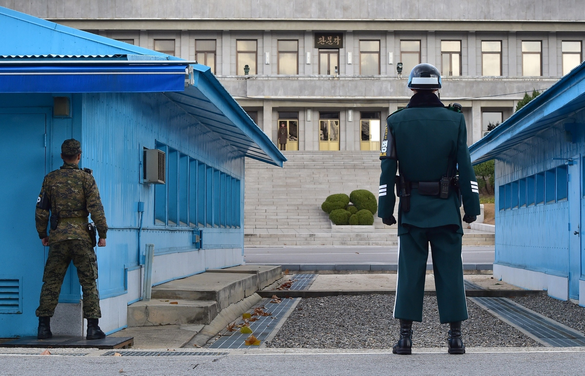 South Korean soldiers stand guard as a North Korean soldier (C back) is seen at the truce village of Panmunjom in the Demilit